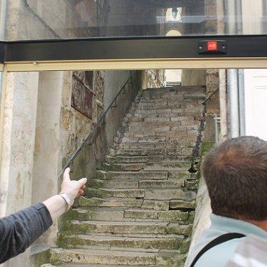 """À droite, le Passage """"Casse-cou"""", une curiosité percée dans la roche. On peut le remarquer également depuis la Place Mirebeau, pris dans un autre sens de la visite où le train passe également pour relier un autre édifice de la visite de la ville basse. L'escalier George Sand est un ancien passage gallo-romain, lequel reliait autrefois ville haute et basse. Le passage ci-dessus accède à la rue Édouard Branly rue du Paradis : bordée d'hôtels des XVIIe et XXIII e siècles"""