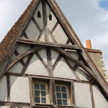 """Cette demeure dite """"des Raisins"""" ou """"de la Vigne"""" comporte un colombage en losanges. La boutique au rez-de-chaussée, est surmontée de deux étages d'habitation desservis par un escalier à vis en bois. Il est situé dans le couloir latéral. La demeure a conservé son décor sculpté dans les sablières de l'étage, et sur les poteaux du rez-de-chaussée, via des motifs de rinceaux de feuillages et de grappes de raisins qui lui ont donné son nom."""